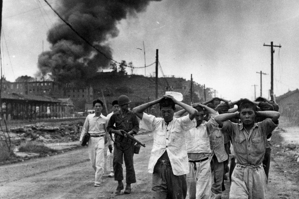 Soldados estadunidenses marcham comunistas da Coréia do Norte por uma estrada de terra, em frente a um vilarejo em chamas. Via Hulton-Deutsch Collection/CORBIS