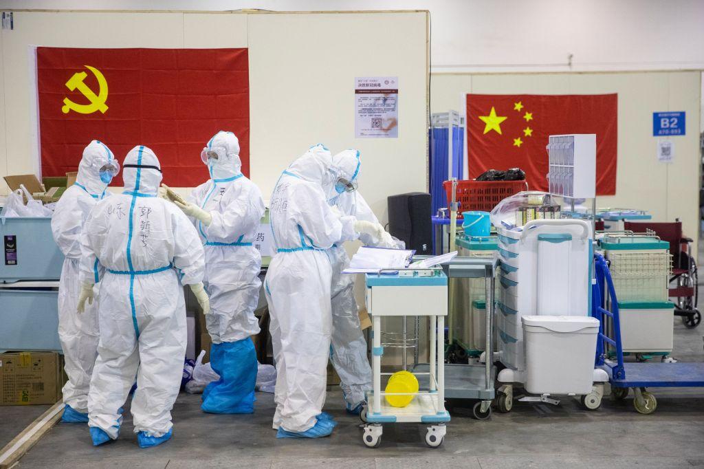 Trabalhadores da saúde chineses trabalham em um centro de eventos convertido em hospital na cidade de Wuhan, 17 de fevereiro de 2020. Via STR/AFP.