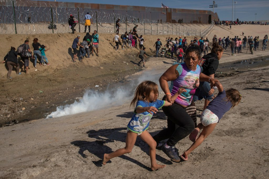 Maria Meza, 40 anos, imigrante de Honduras, parte de uma caravana que busca a entrada para os Estados Unidos, foge do gás lacrimogêneo com suas filhas gêmeas, Saira Mejia Meza (esquerda) e Cheili Mejia Meza (direita) em frente ao muro da fronteira com o México, em Tijuana, no dia 25 de novembro de 2018. Foto de Kim Kyung Hoon.