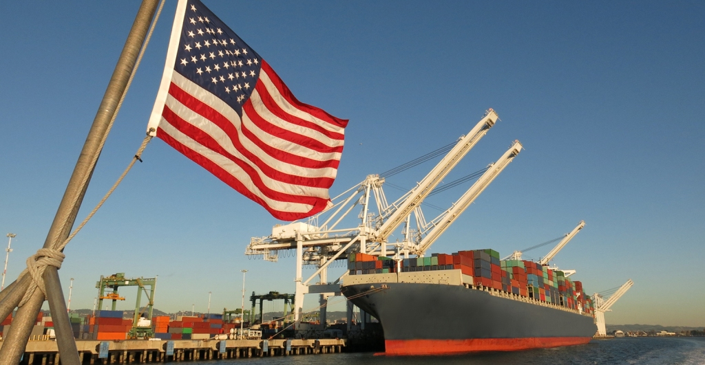 """Uma bandeira estadunidense balança com um porto ao fundo, com um cargueiro carregado de conteineres. A imagem simboliza o """"Made in America"""" e o poder econômico do país norte-americano. Via mpexa.com"""