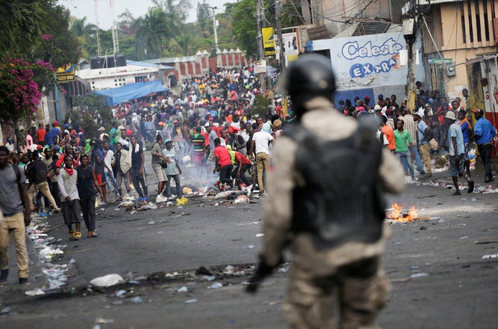Manifestantes reinvindicando a renúncia do presidente Jovenel Moise enfrentaram a política em Porto Príncipe. Foto por Andres Martinez Casares/Reuters.