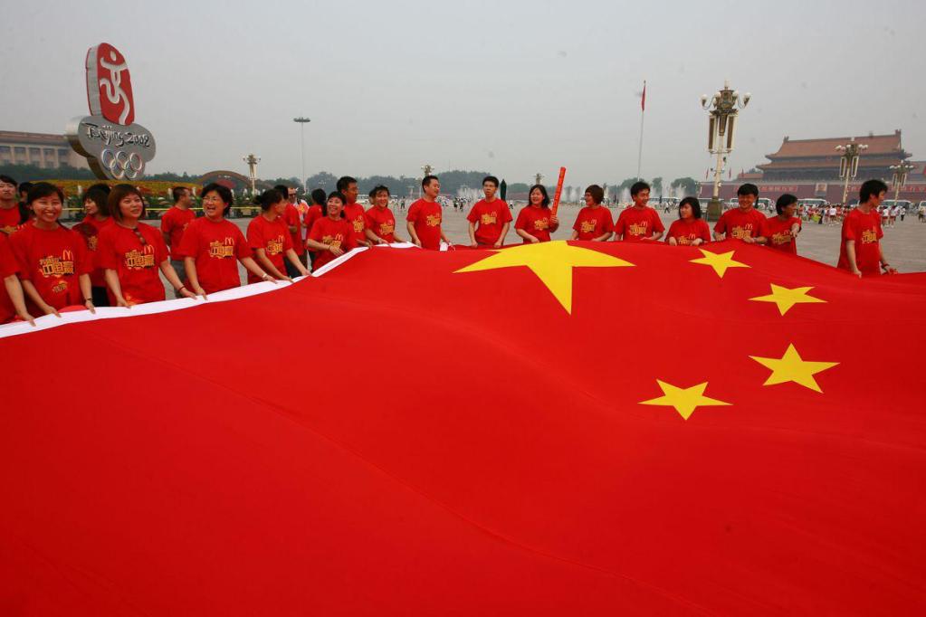 Chineses segurando a bandeira nacional durante os Jogos Olímpicos de 2008, em Pequim.