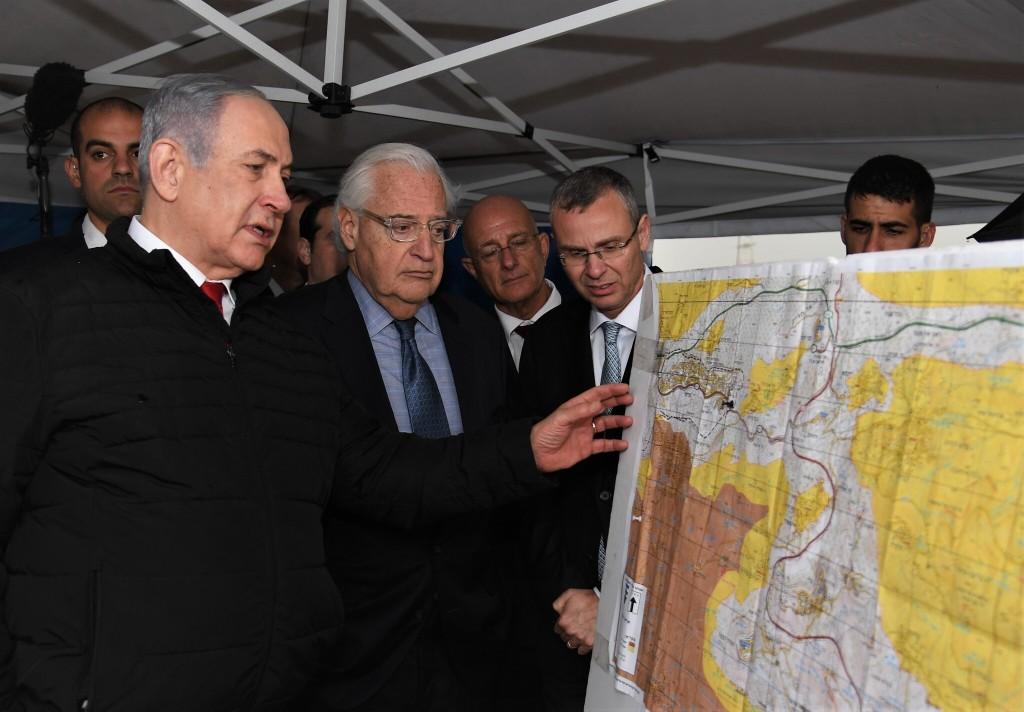 Primeiro-ministro israelense Benjamin Netanyahu (esquerda) e embaixador estadunidense em Israel David Friedman (centro), e o Ministro do Turismo israelense Yariv Levin (direita) durante reunião sobre o mapeamento da soberania de Israel sobre áreas da Cisjordânia, no assentamento Ariel, 24 de fevereiro de 2020. Foto por David Azagury/US Embassy Jerusalem.