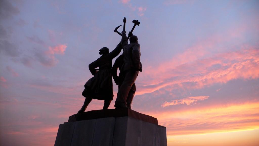 Foto das estátuas de bronze em frente à Torre Zuche, em Pyongyang. Representam um operário, um intelectual e uma camponesa, segurando um martelo, um pincel e uma foice, símbolo do Partido dos Trabalhadores da Coreia. Via https://mansudae-korea.com/