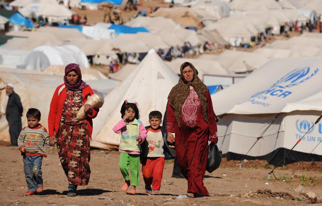 Refugiados sírios andam no campo de Atme, próximo à fronteira turca ao noroest da Síria, na província de Idlib, no dia 29 de março de 2013. Foto por Bulent Kilic/AFP.