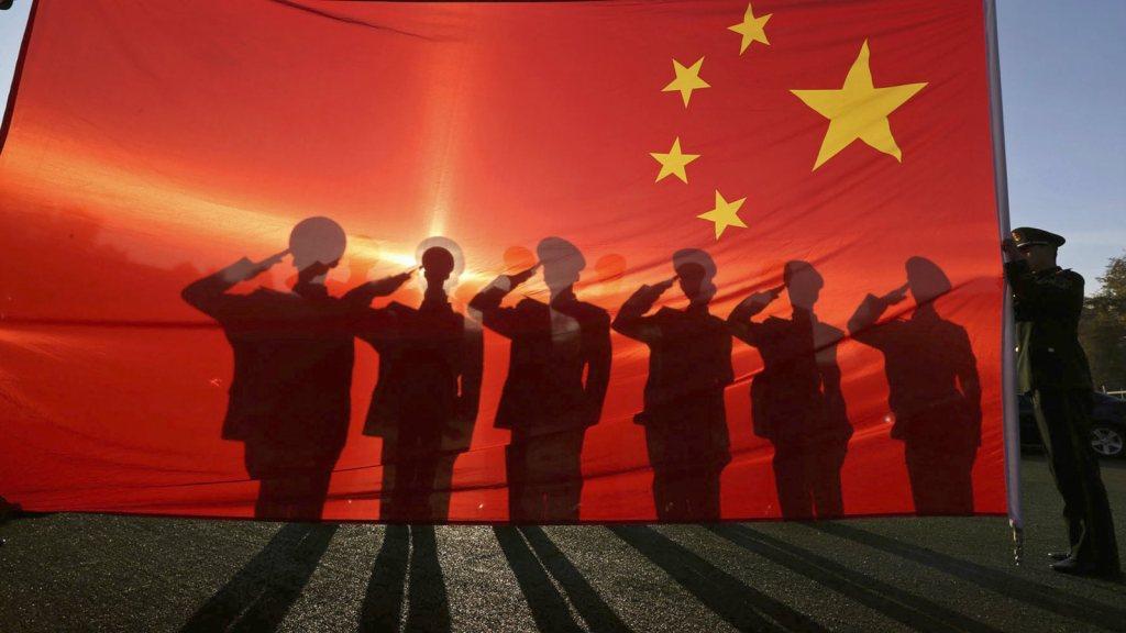 Militares chineses em frente a bandeira vermelha do gigante asiático. Via Reuters.