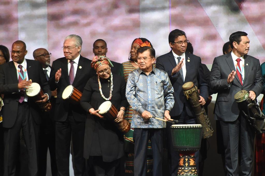 Vice-presidente indonésio (à frente, à direita) toca tambores com os delegados durante a abertura do Fórum Indonésia-África (IAF) 2018 em Nusa Dua, na Indonésia, no dia 10 de abril de 2018. Via AFP/Sonny Tumbelaka