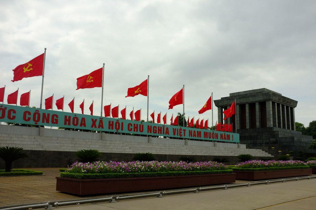 Fachada do mausoléu de Ho Chi Minh, com as bandeiras do Partido Comunista ao lado das bandeiras nacionais do Vietnã. Via flickr.