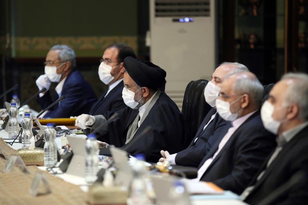 Reunião em Teerã com os membros do governo, todos utilizando máscaras e luvas, no dia 18 de março de 2020. Via Presidência Iraniana/AP.