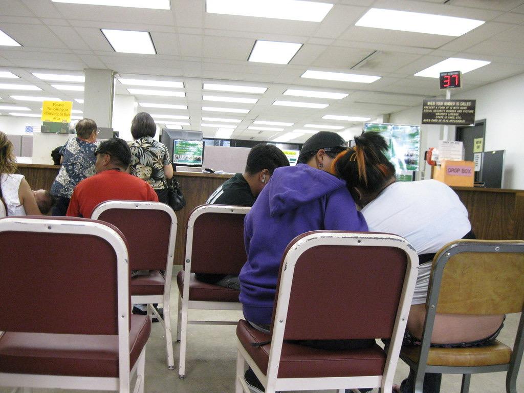 Famílias esperam atendimento na secretaria seguro-desemprego. Foto por Burt Lum.