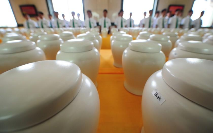 Um grupo de funcionários atrás de uma exposição de urnas funerárias biodegradáveis em um cemitério em Tianjin, ao norte da China, no dia 20 de julho de 2010. Foto por Frederic J. Brown/AFP.