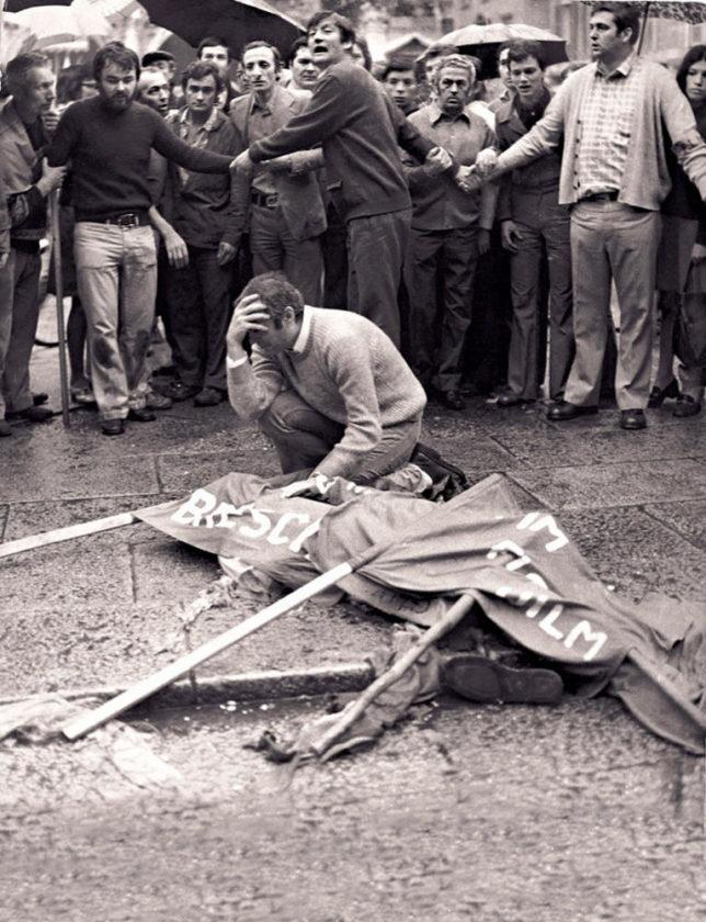 Um homem chora sobre o cadáver de seu irmão, coberto com bandeiras, morto por consequência de uma bomba plantada pelo grupo de extrema-direita Ordine Nuovo na Piazza della Loggia, em Bréscia, durante uma manifestação antifascista em 1974. Foto via Archivos de la Historia.