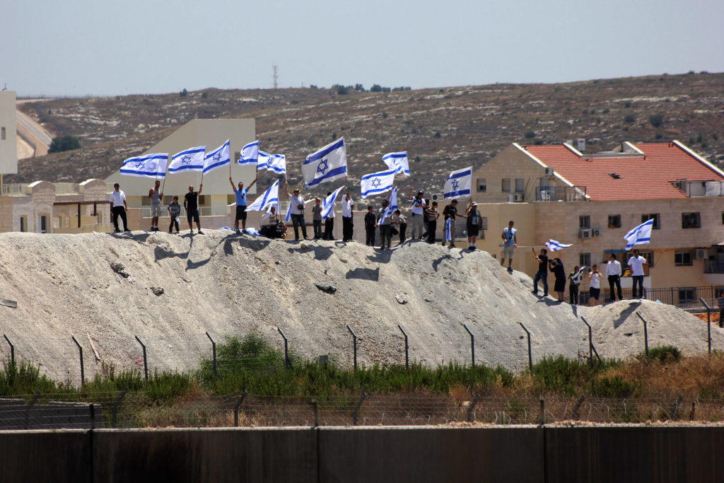 Israelenses do assentamento ilegal de Modi'in Illit levantam bandeiras de Israel e cantam slogans contra os manifestantes palestinos do outro lado do muro, durante uma manifestação contra a ocupação israelense e o muro de separação no vilarejo de Bil'in na Cisjordânia, em 28 de junho de 2013. Foto por Ahmad Al-Bazz.