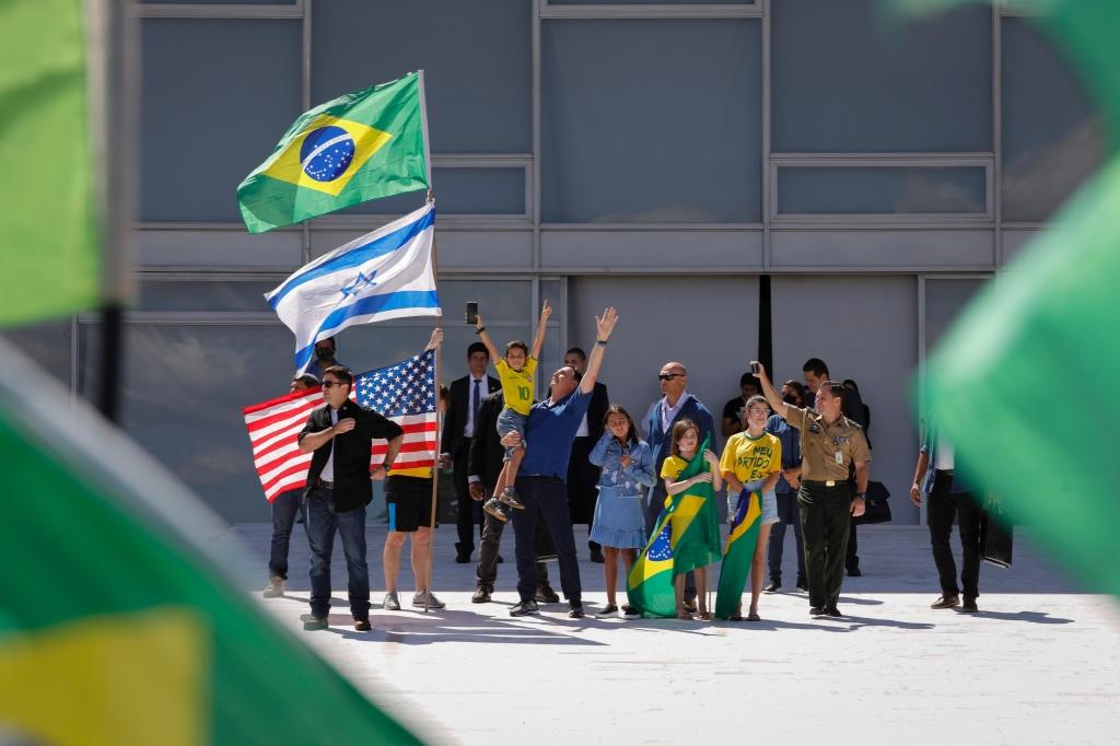 Bolsonaro esqueceu (ou e$$$queceu) a qual país serve como presidente, ainda que de forma fraudulenta, e posou sob as bandeiras do imperialismo anglo-sionista, o que por si só deveria ser um motivo para a revolta popular. Você já viu uma foto de um presidente destes países posando sob a bandeira brasileira? Pois é.