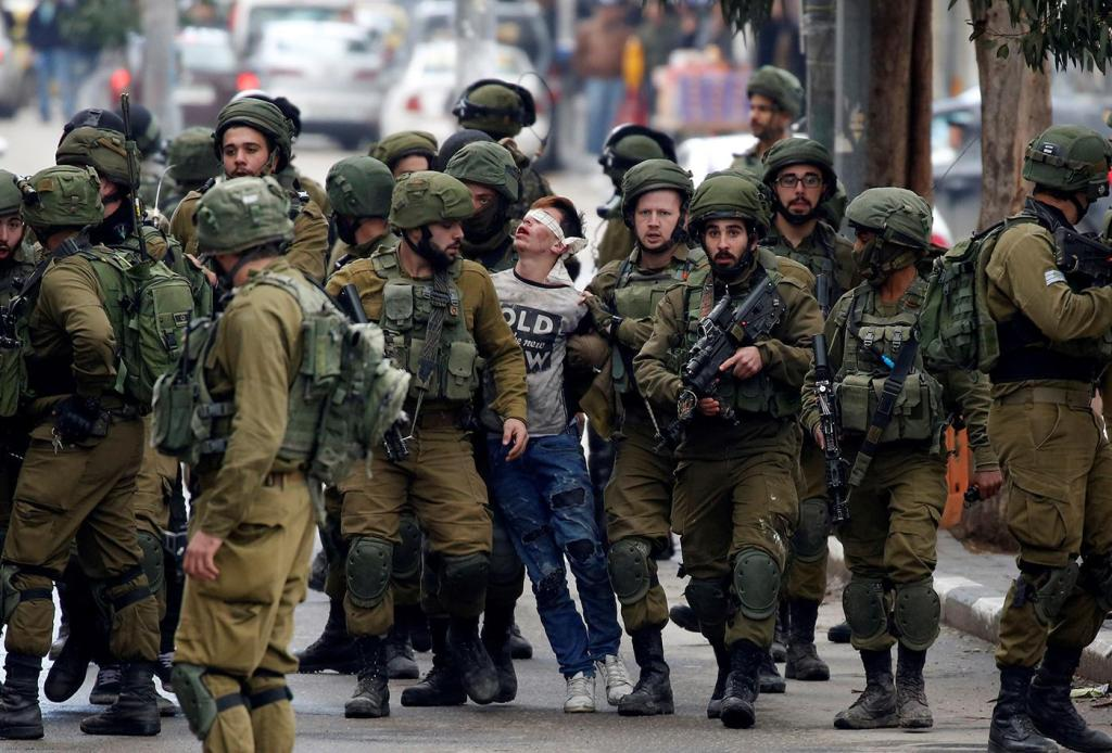 Soldados israelenses prendem Fawzi al-Junaidi, um jovem de 16 anos, em Hebrom, durante protestos contra a decisão estadunidense de reconhecer Jerusalém como a capital de Israel, em dezembro de 2017. Foto por Wisam Hashlamoun.