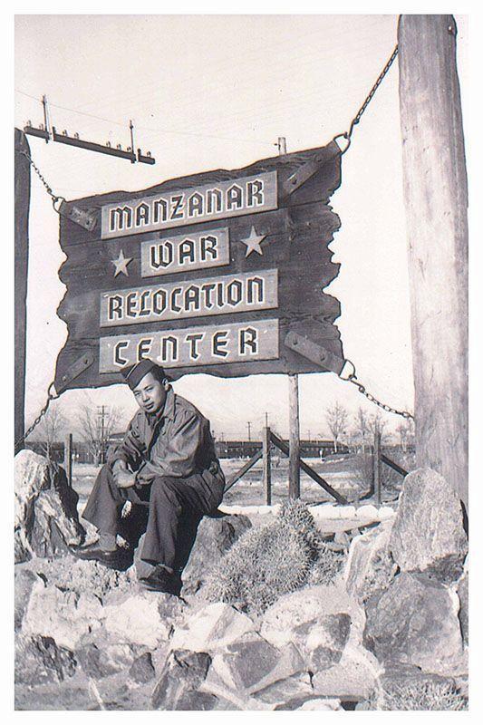 O soldado Ben Hatanaka, sob licença do exército estadunidense, senta-se sob a placa de entrada do Campo de Manzanar durante visita a familiares internados. Foto via nippon.com