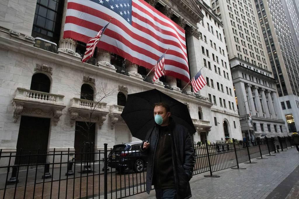 Um homem caminha em frente ao New York Stock Exchange. Foto via AP.