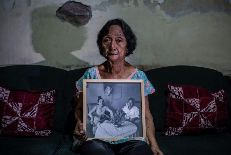 Sri Muhayatty, 75 anos, segurando uma fotografia de seus pais, no dia 6 de maio de 2016, em Yogyakarta, Indonésia. Estudante em 1965, passou 5 anos presa sem julgamento por supostas ligações com comunistas, enquanto seu pai desapareceu, presumidamente vítima de uma execução extra-judicial. Foto por Ulet Ifansasti.