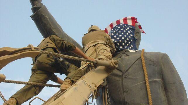 Tropas estadunidenses colocando uma bandeira dos Estados Unidos sobre uma estátua de Saddam Hussein em 2003. Foto via El Diario.