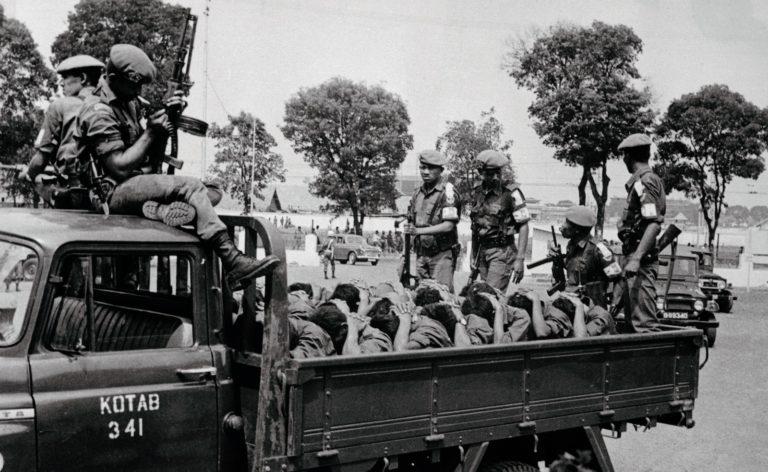 Um grupo de jovens supostamente comunistas sendo transportados pela polícia militar em Jacarta, Indonésia, no dia 10 de outubro de 1965. Foto por Bettmann.