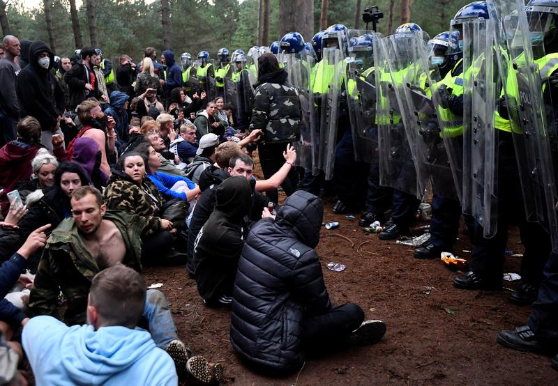 Policiais interrompem uma festa ilegal em uma floresta na Inglaterra, em meio às restrições devido ao coronavírus. Foto por Toby Melville.