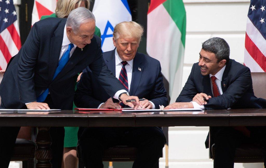 O primeiro-ministro israelense Benjamin Netanyahu, o presidente estadunidense Donald Trump e o chanceler dos Emirados Árabes Unidos, Abdullah bin Zayed Al-Nahyan, assinam os Abraham Accords no dia 15 de setembro de 2020. Foto via AFP.
