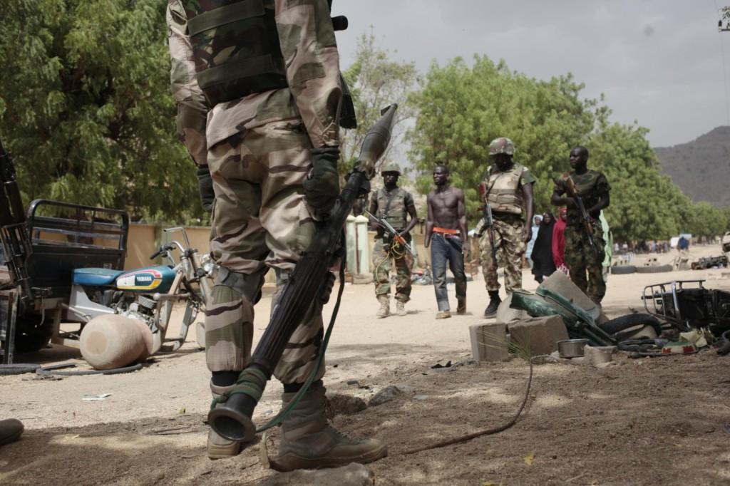Soldados nigerianos escoltam um homem escravizado pelo Boko Haram em Gwoza. Foto por Lekan Oyekanmi.