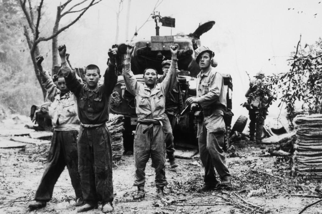 Fuzileiro naval estadunidense escolta prisioneiros de guerra norte-coreanos em 1953.