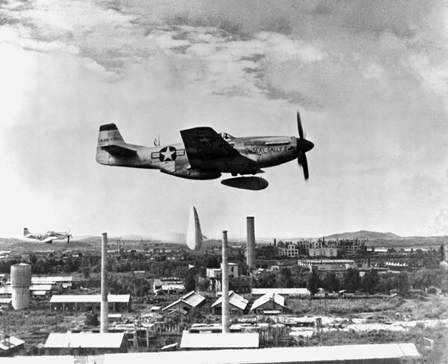Caça Mustang P-51 da US Air Force lançando duas bombas de napalm na Coreia do Norte, em janeiro de 1951.
